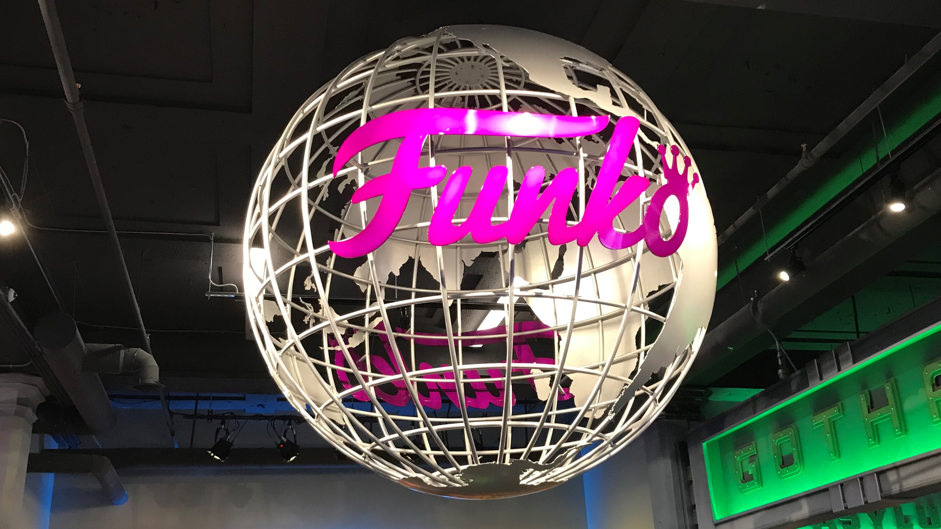 a silver painted steal globe hanging from the acieling adorn with a bright pink Funko store logo