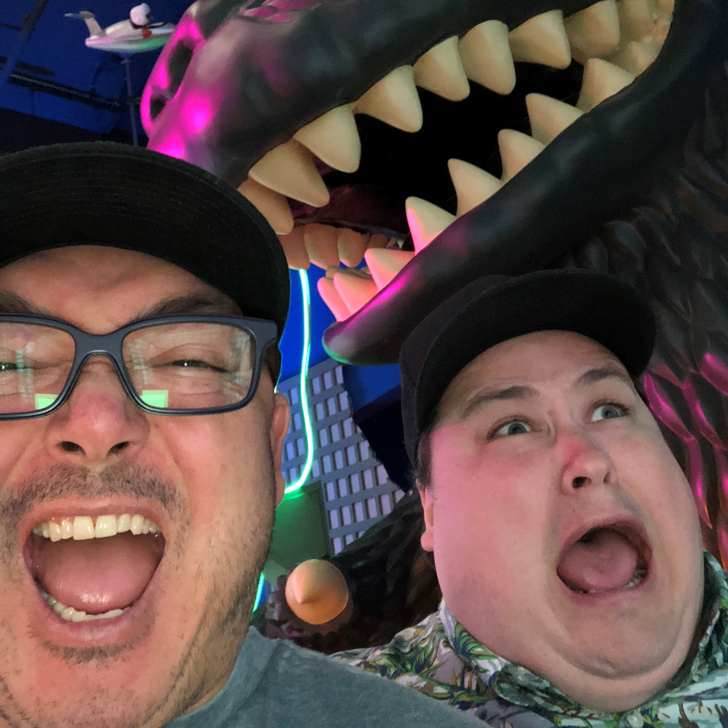 two terrified mens faces who apear to be fleaing from a Godzilla statue towering above them